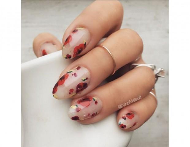 Una base semi trasparente e unghie dalla forma a mandorla, con una cascata di petali rossi. Photo credits @NinaNailedit