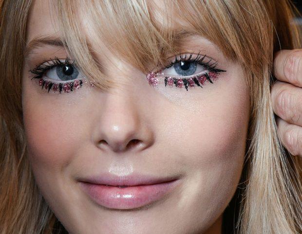 Glitter e ciglia disegnate con l'eyeliner lungo la rima inferiore.
