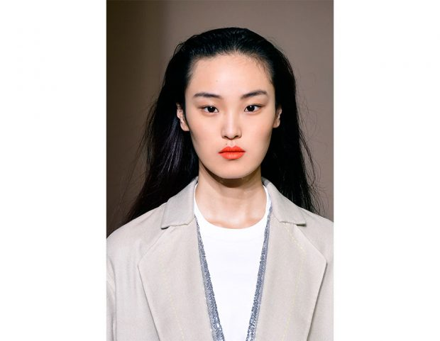 Rossetto aranciato come elemento centrale del look.