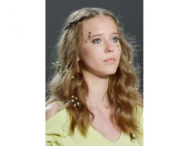 Ispirazione hippie con treccine e fiori tra i capelli.