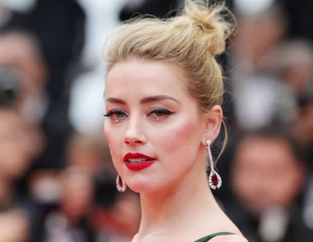 Messy bun, eyeliner e rossetto rosso per Amber Heard. Make up by L'Oréal Paris. (Photo credit: Getty Images)