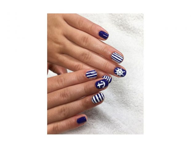 Nail art bianca e blu con righe, àncore e timoni. (Photo credit: instagram @jannikeivalje)