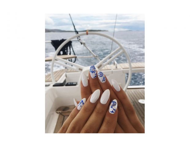 Nail art bianca con decorazioni a mano libera blu. (Photo credit: instagram @sylwianowak)