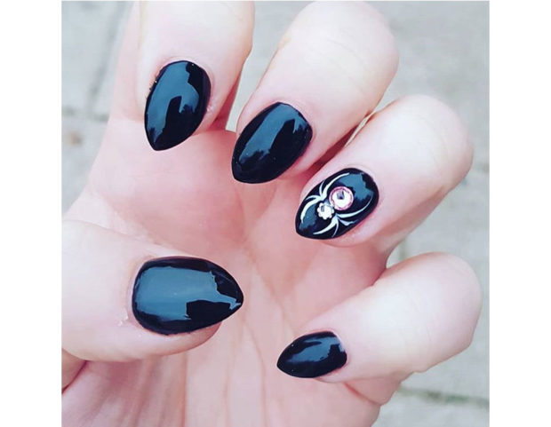 Smalto nero lucido con accent nail di cristalli, con ragno stilizzato. Photo credit: Instagram @captainchar